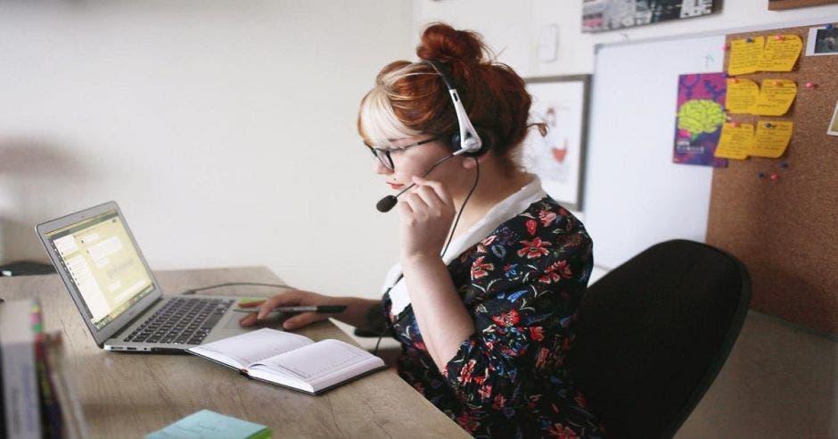 Una mujer con una computadora y audífonos