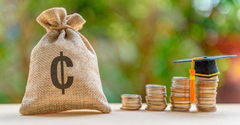Bolsa de dinero con signo de colones y fila de monedas