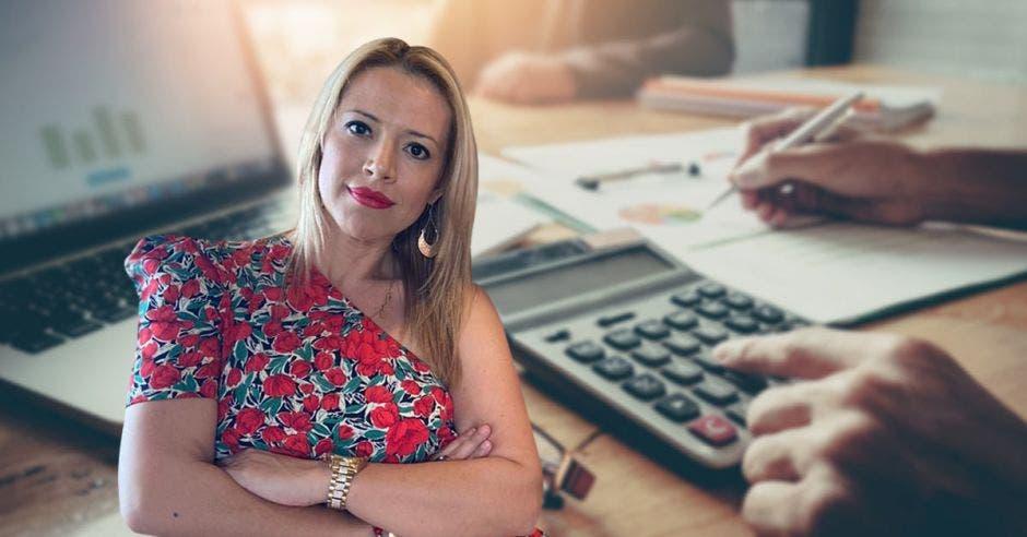 Una mujer con blusa floreada posa junto a una calculadora