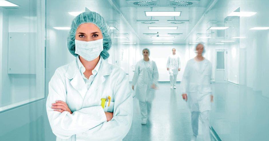 Mujer con tapabocas y bata de doctora en pasillo