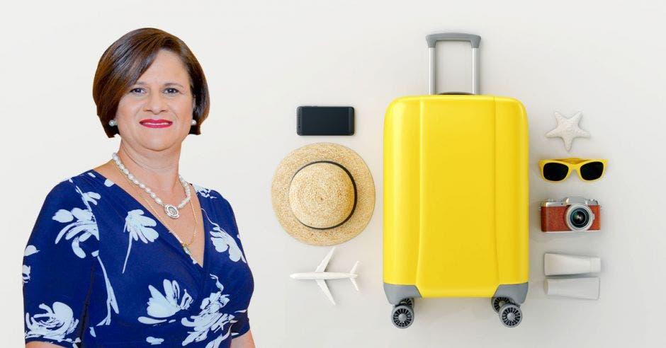Una mujer de vestido azul posa junto a una valija amarilla