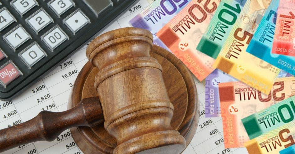 Mazo de juez junto a billetes y calculadora