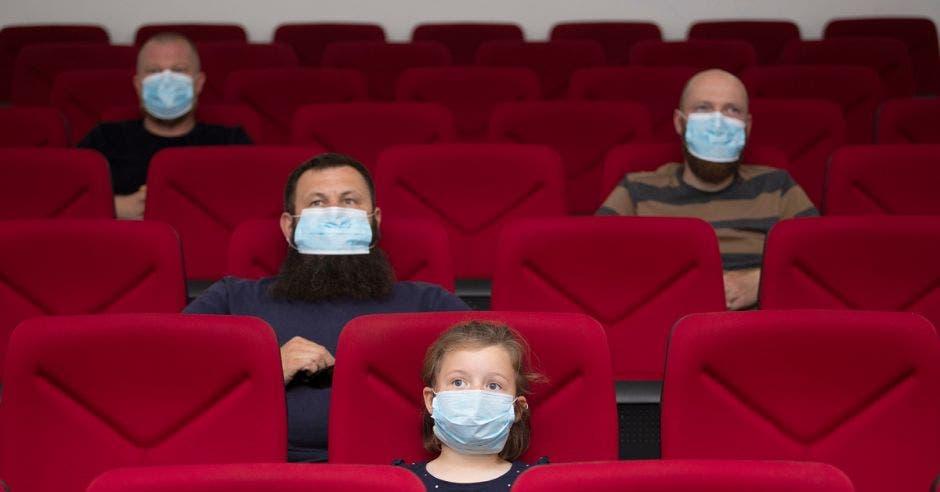 Personas en el cine con mascarillas