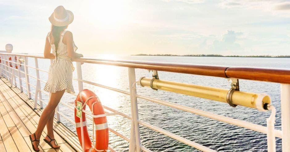Una turista se apoya sobre la baranda de un crucero, mirando un atardecer