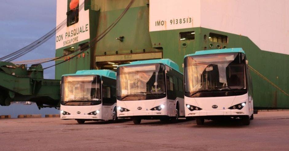 Tres buses electricos color blanco junto a un buque de gran tamaño