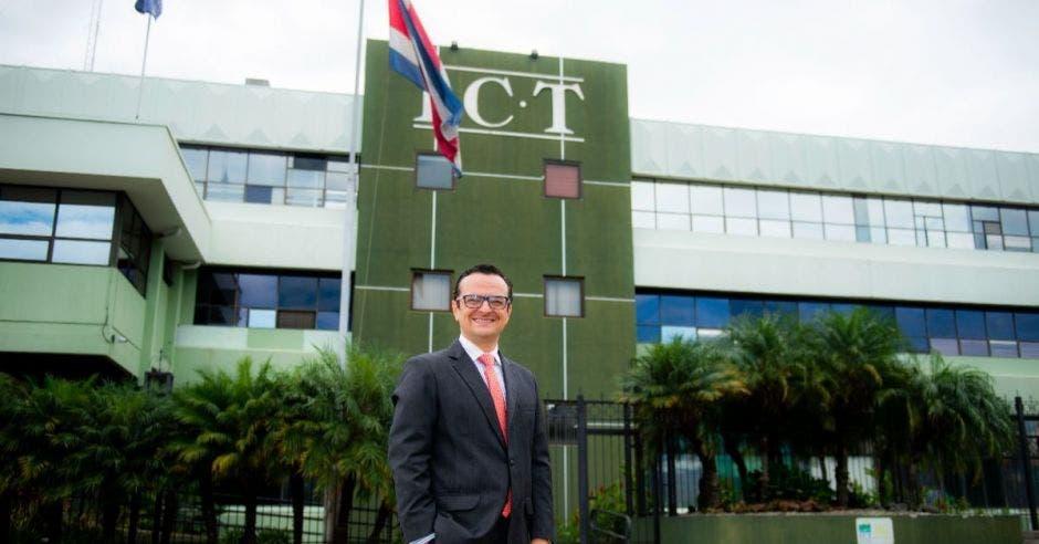 Un hombre de saco y corbata posa junto a un edificio de color verde