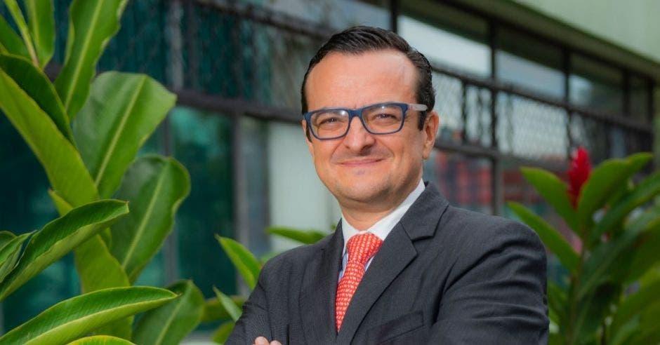 Un hombre con anteojos sonríe frente a un edificio color gris