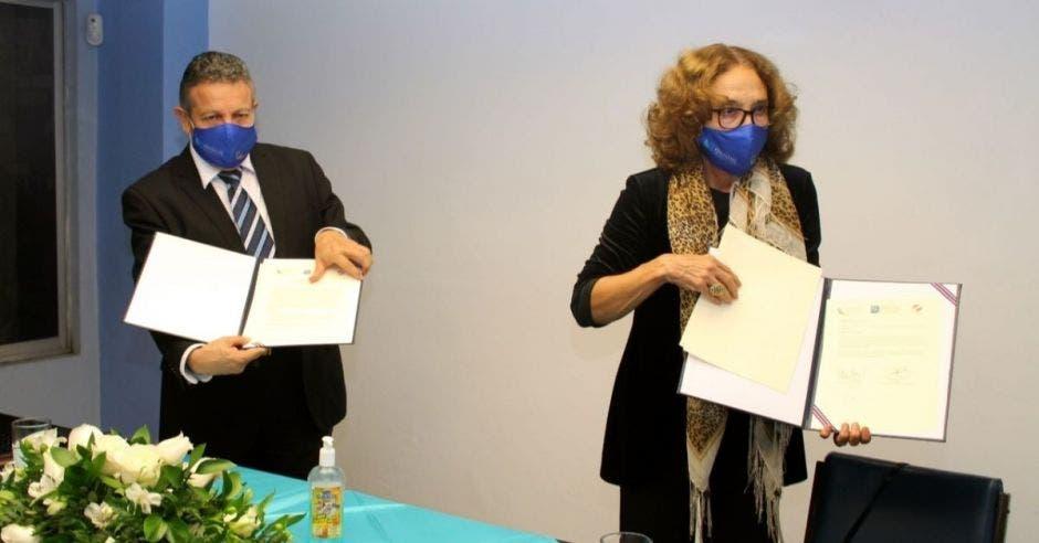 Un hombre y una mujer sostienen una serie de documentos