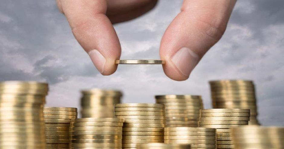 Monedas siendo apiladas por mano grande