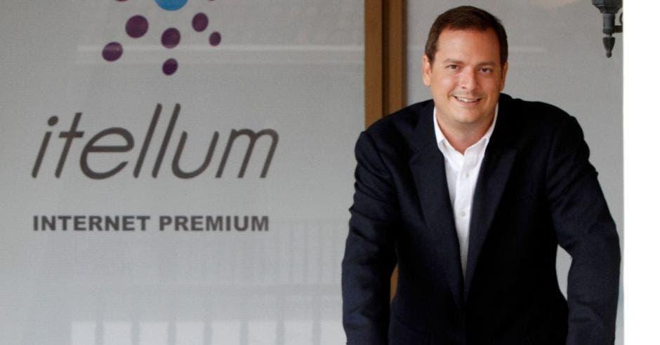 Un hombre con saco negro y camisa blanca posa  junto a un letrero que dice Itellum