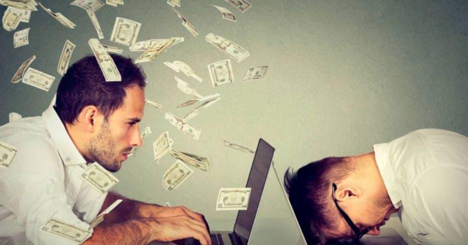 Persona viendo computadora y otra con cabeza agachada y dólares volando