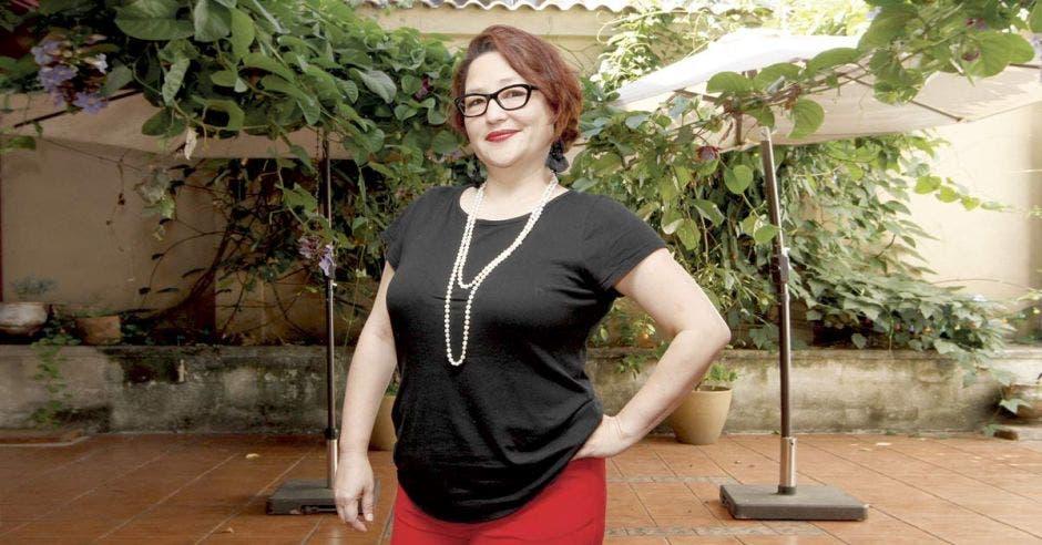 Una mujer con blusa negra y pantalón rojo.
