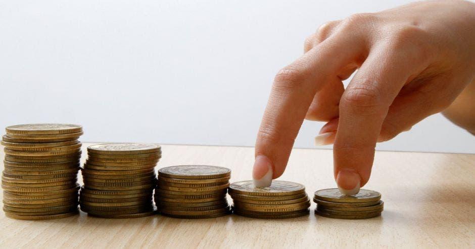 Dedos de mujer suben escalera de monedas