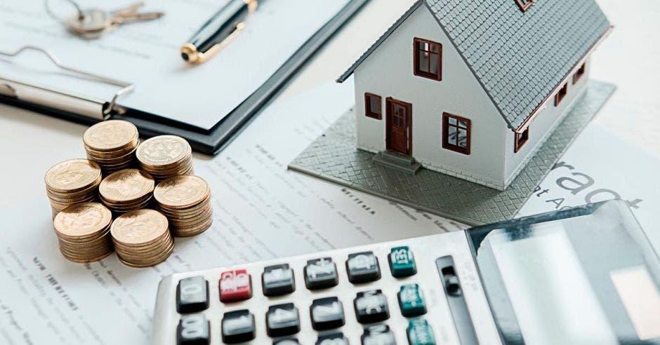 Calculadora, monedas y casa miniatura