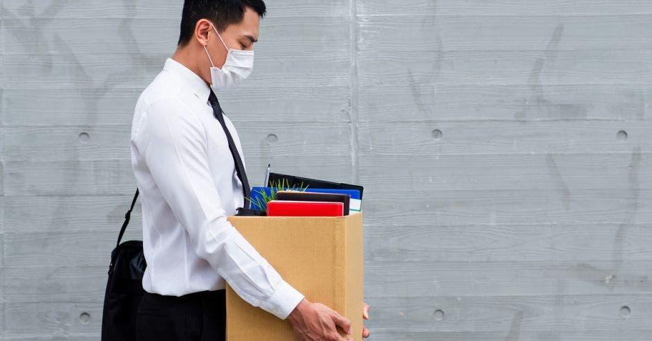 Un hombre con mascarilla recoge una caja de su oficina