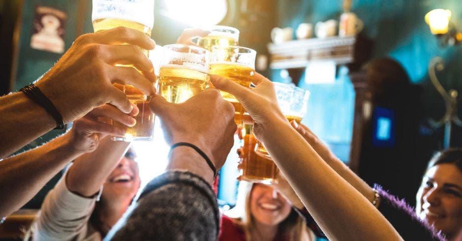 Un grupo de amigos choca sus cervezas sobre sus cabezas
