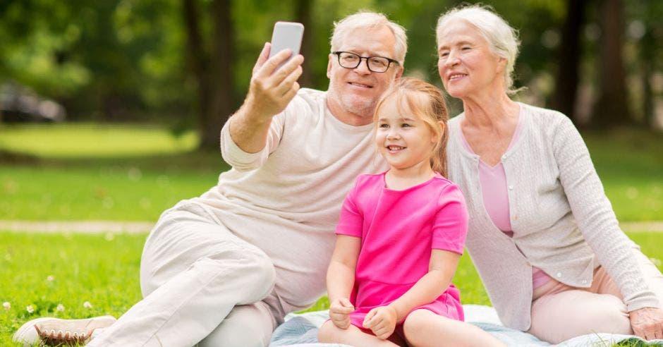 Adultos mayores y jóvenes viendo celular