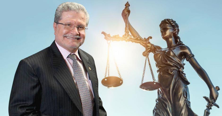 Un hombre mayor de bigote sonríe junto a una estaua de la justicia