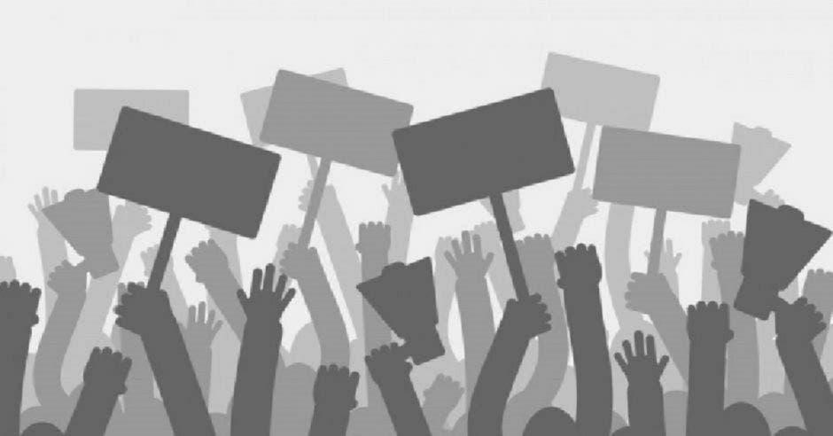 Un conjunto de manifestantes alza pancartas en forma de protesta