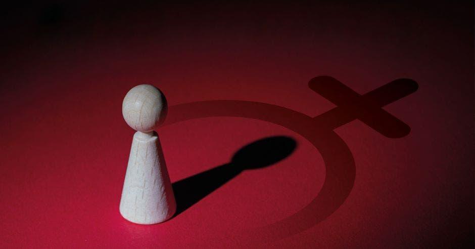 una ficha de peón de ajedrez color blanco sobre un fondo rojo