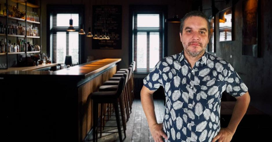 un hombre con camisa floreada parado junto a la barra de un bar