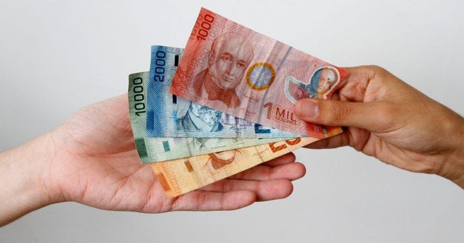 Hombre dando billetes a otro