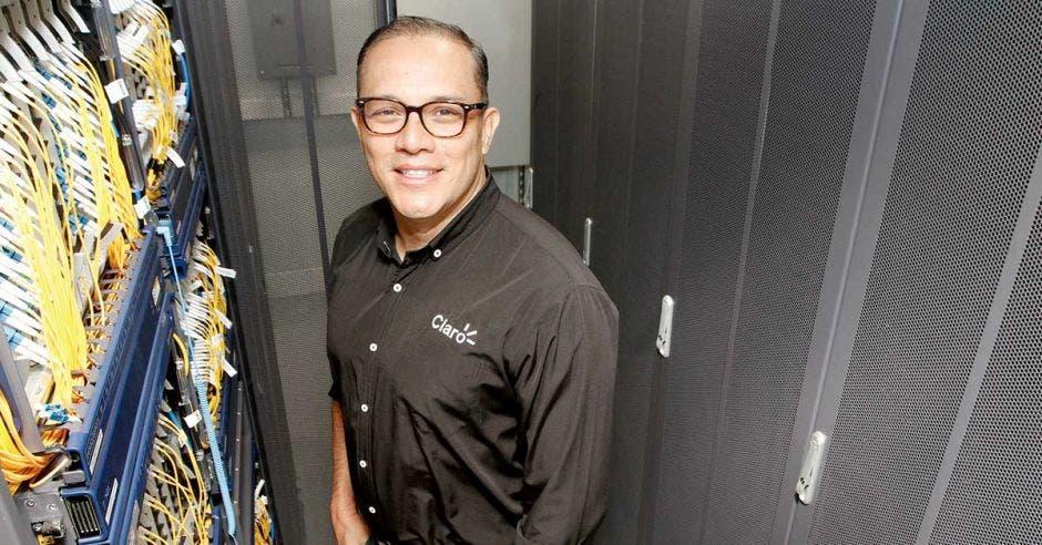 Un hombre de anteojos y camisa negra posa en medio de varios routers