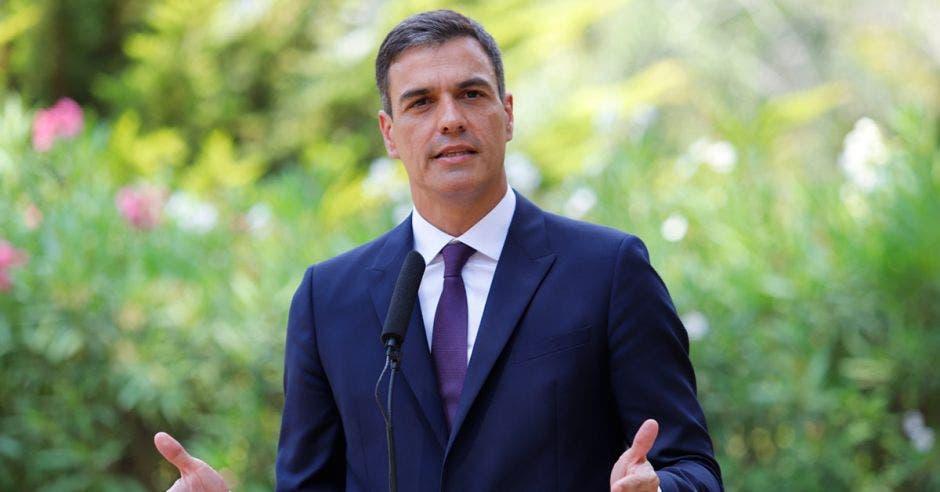 Un hombre de traje y corbata habla frente a una audiencia