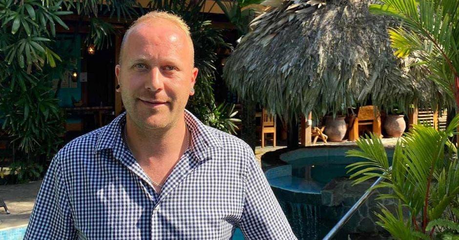 Un hombre caucásico con camisa a rayas sobre el fondo de un hotel con rancho y piscina