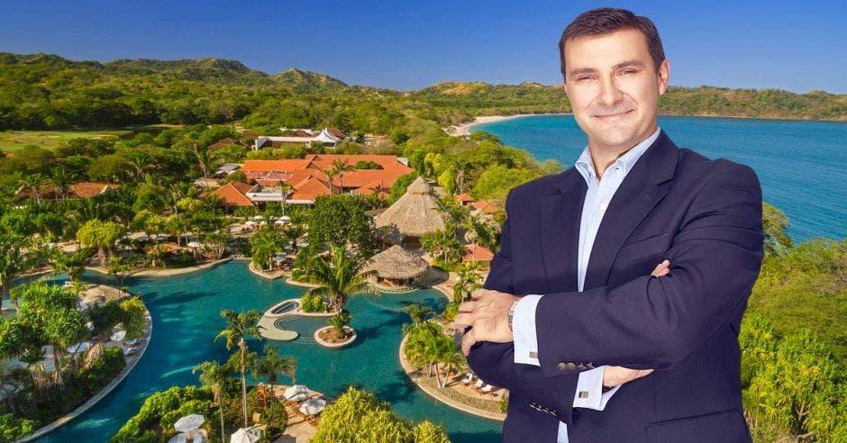 un hombre con saco sobre un fondo que tiene hoteles y piscinas