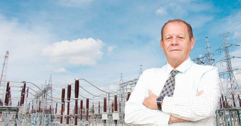 un hombre mayor con camisa blanca y corbata sobre un fondo de antenas