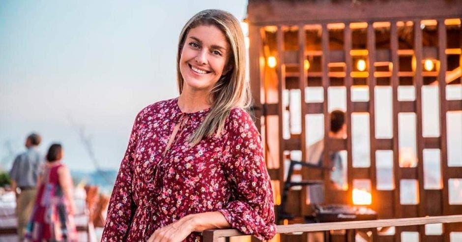 una mujer con vestido floreado apoyada sobre una baranda de madera