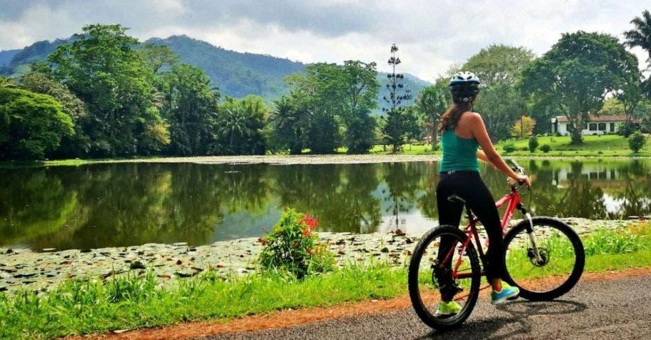 Una mujer en bicicleta mira un lago