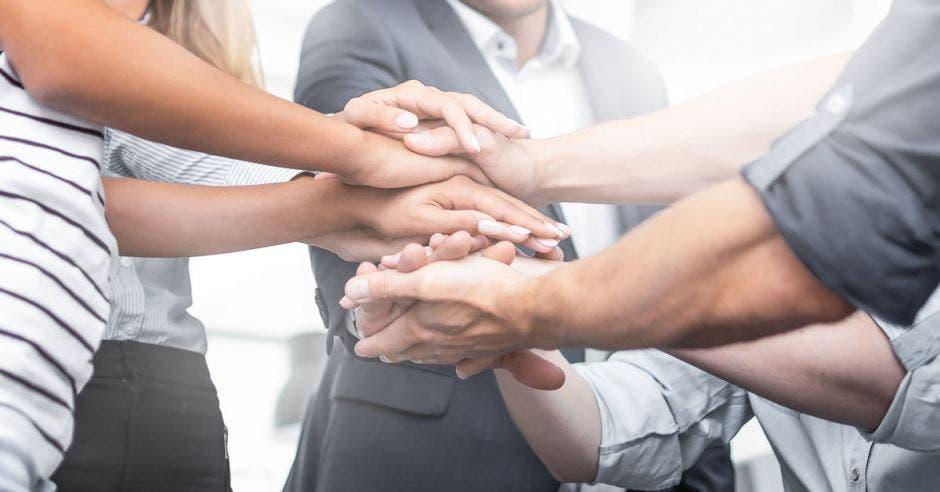 Personas uniendo manos