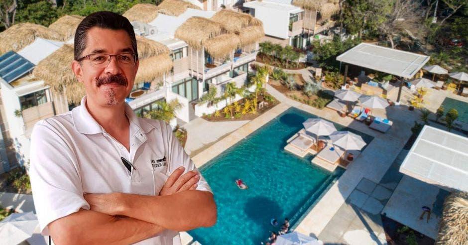 Un hombre de bigote y camisa blanca posa sobre la imagen de un hotel