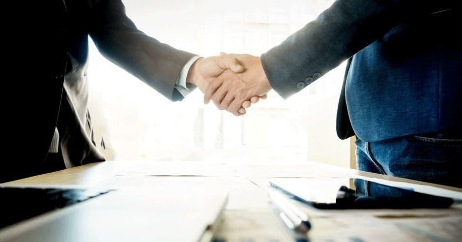 dos hombres se estrechan la mano junto a una mesa