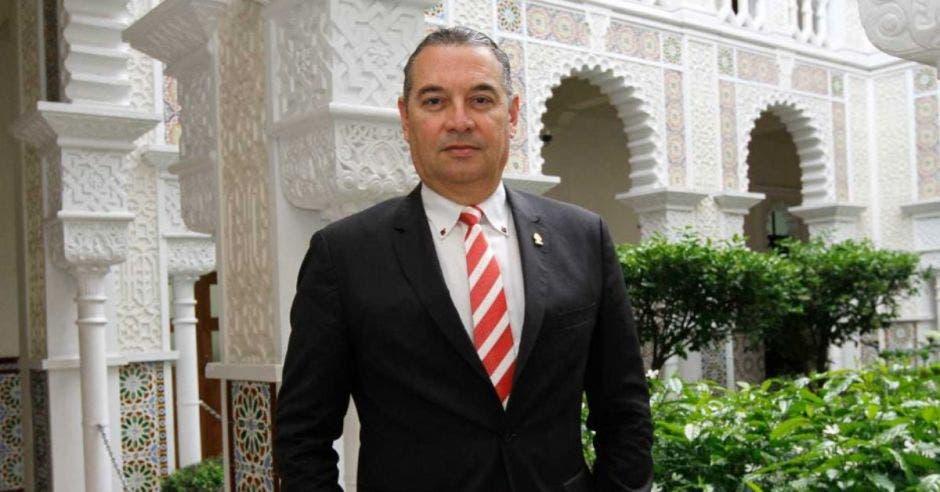 Un hombre con saco oscuro y corbata blanca a rayas con rojo