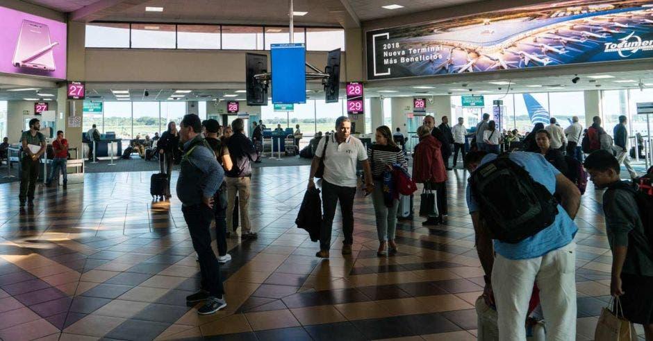 una multitud recorre el lobby de un aeropuerto