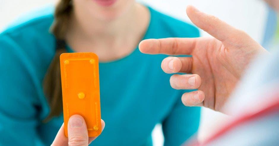 Una joven con una pastilla y un doctor