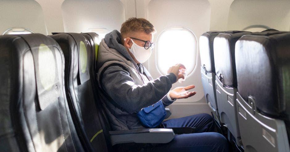 Un hombre se aplica alcohol en gel mientras está sentado en un avión