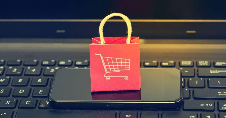 Una bolsa de compras sobre un celular y una computadora