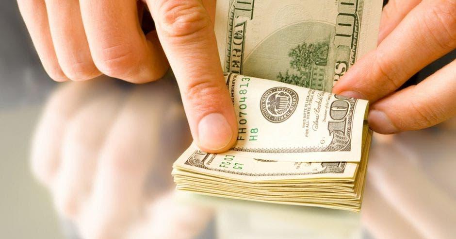 Persona contando dólares