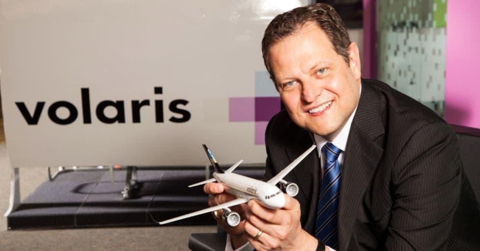 un hombre de tez clara y ojos azules sostiene un avión d ejuguete
