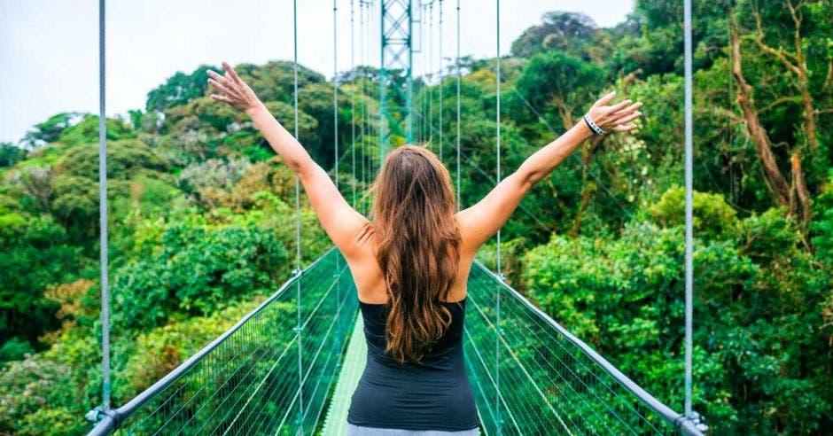 Una mujer con las manos abiertas en un puente colgante