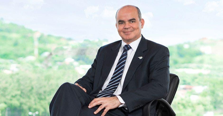 Un hombre calvo de traje oscuro y corbata azul sentado sobre una silla
