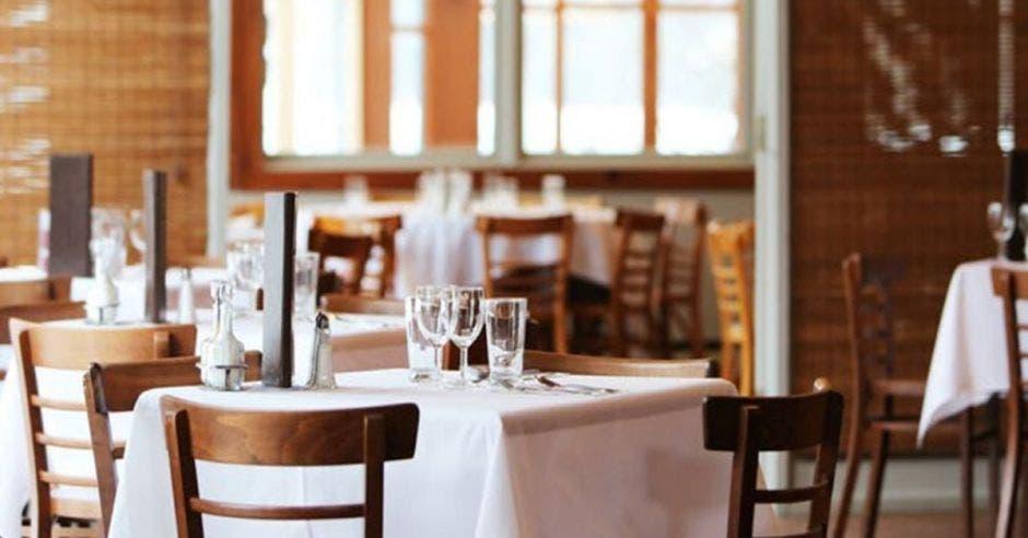 Una mesa con manteles blancos y vajillas de vidrio