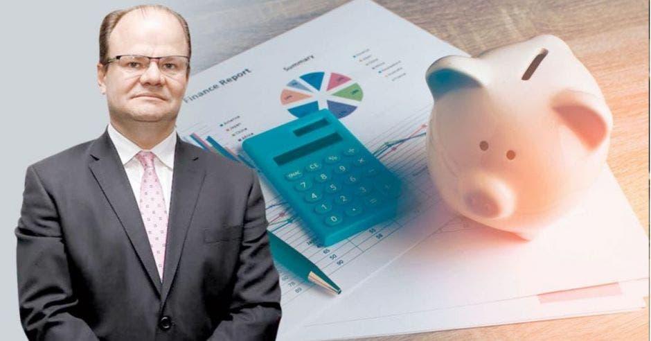 un hombre calvo junto a una calculadora y un cerdito de ahorros