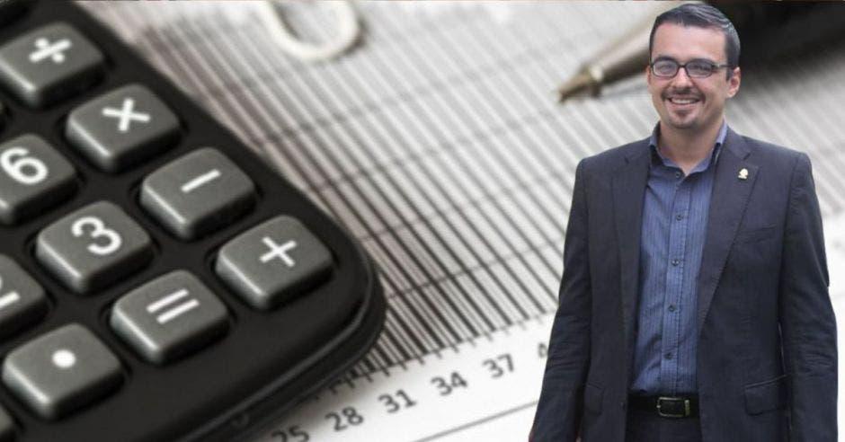 un hombre con anteojos y traje posa junto a una calculadora
