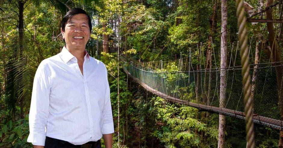 Un hombre asiático de camisa blanca sobr eun puente colgante