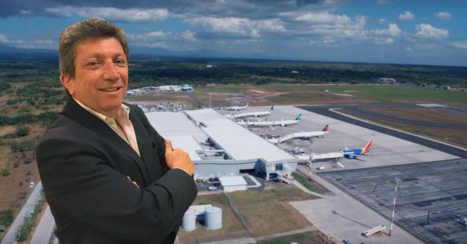un hombre con saco posa frente a un aeropuerto